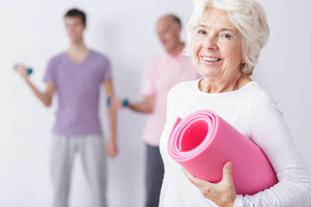 health elderly: Photo of happy elderly woman at gym after training
