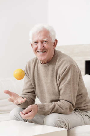 tossing: Happy old man is tossing an orange