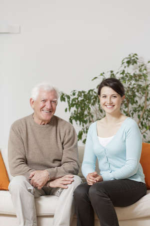 Happy old man sitting next to young family member Stock Photo