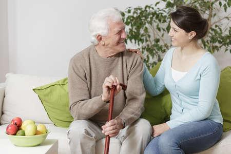 vejez feliz: Viejo hombre que sostiene un bastón y sonriendo a la mujer joven