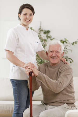 ambulant: Young nurse caring for old man with walking stick
