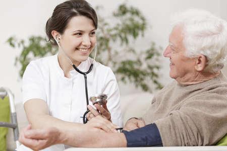 enfermeria: Sonriente joven enfermera toma la presión arterial del anciano