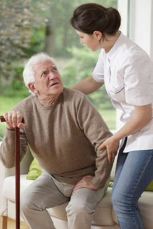 ambulant: Woman helping old man to stand up Stock Photo