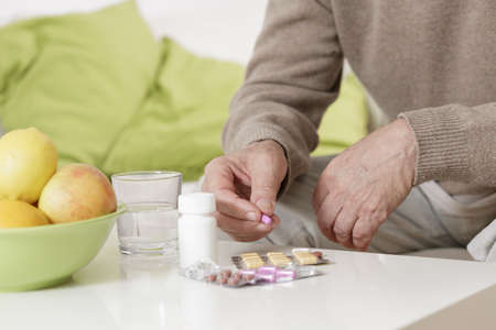 ailing: Ailing old man taking pills with water Stock Photo