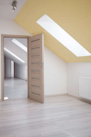 attic: Attic room with white walls and yellow ceiling Stock Photo