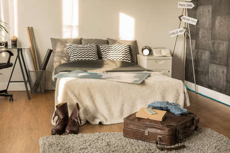 bedroom bed: Picture of traveler bedroom with decorative signpost and large bed Stock Photo