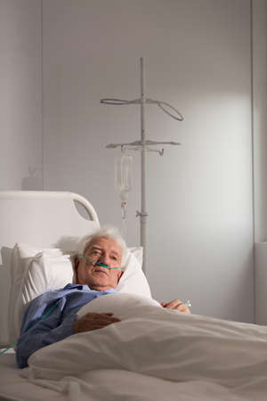 palliative: Lonely elder patient on a drip in hospital