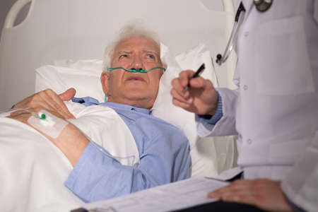 examined: Elderly man in bed examined by doctor