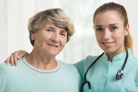 care at home: Smiling elderly lady with her supportive doctor