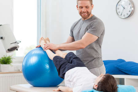 therapy room: Little boy doing exercise with large ball