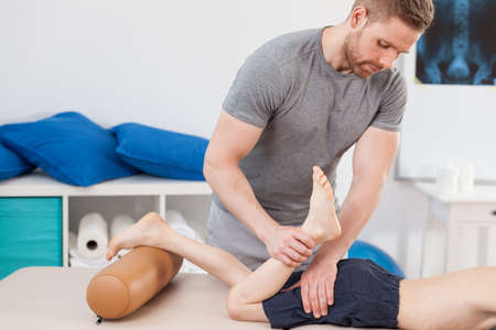 physiotherapy: Image of male chiropractor stretching boys leg Stock Photo