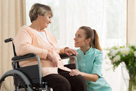 nursing assistant: Elderly woman on wheelchair in nursing home with her care assistant
