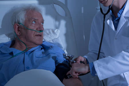 examined: Recovering senior patient examined by doctor in hospital Stock Photo