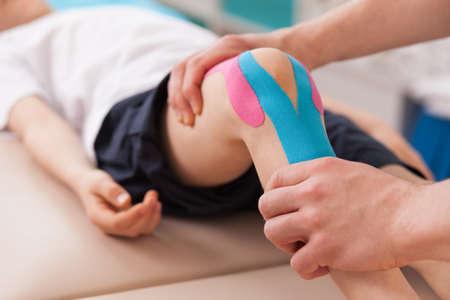 kinderschoenen: Fysiotherapeut doen met kind oefening voor de knie Stockfoto