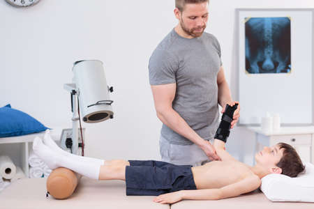 treating: Image of pediatric physiotherapist treating little patient