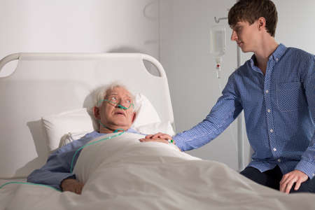 hospice: Elderly hospice patient with caregiver supporting him