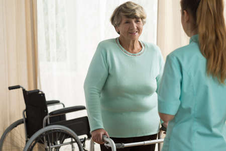 lady doctor: Disabled smiling elderly lady with a walking frame Stock Photo