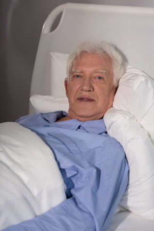 geriatrics: Suffering old man spending time alone in hospice Stock Photo