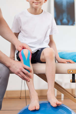 taping: Child with kinesio taping application on the knee