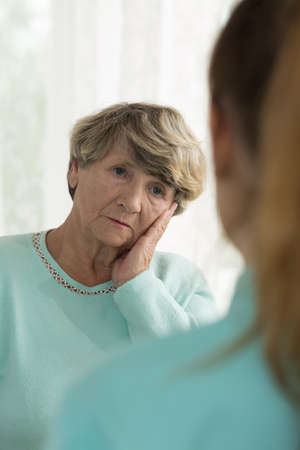 senior female: Worried elderly woman hearing bad news from a doctor