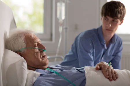 hospice: Sleeping elderly hospice patient with a carer