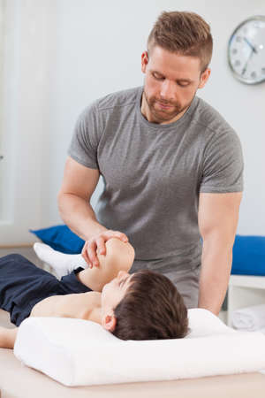 therapy room: Physical therapist stretching young patient with cerebral palsy Stock Photo