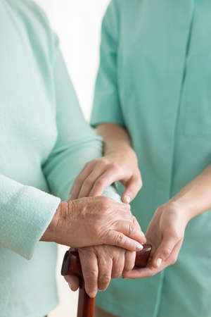 home health care: Close-up on senior womans hands on a walking stick