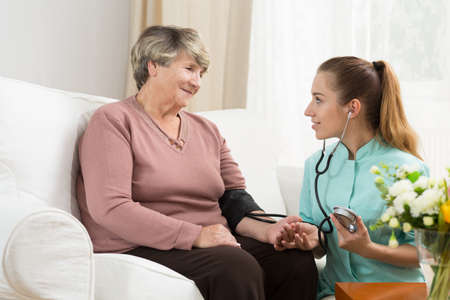 Care assistant and senior lady in nursing home Imagens