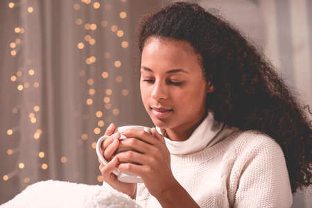 cosy: Image of winter girl in cosy room with decorative lighting