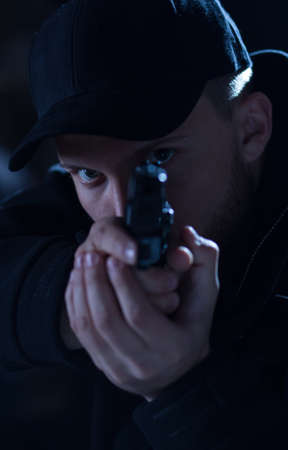 cop: Young male cop under cover shooting from gun Stock Photo