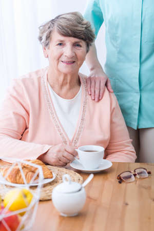 Picture of elderly patient with indigestion problem drinking tisane Stock Photo