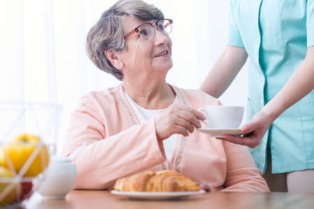 indigestion: Picture of senior woman drinking tea for indigestion Stock Photo