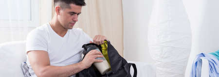 water bottle: Young man packing his backpack before gym