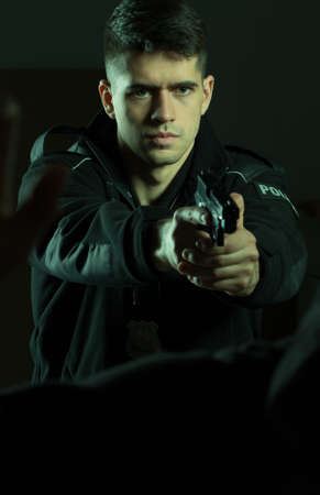 self defense: Young armed policeman with gun and self defense Stock Photo