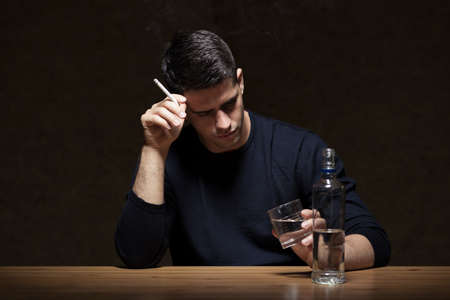 alcoholic man: Young man is smoking and drinking some vodka