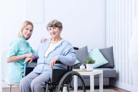 paciente: Foto de la mujer de edad avanzada con discapacidad y cuidadores