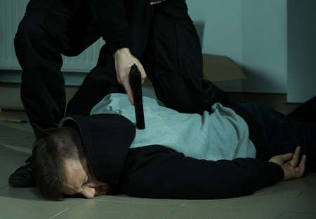 ground: Caught suspect lying on ground pressing by cop Stock Photo