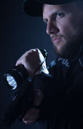 security guard: Careful young policeman lightening with flashlight