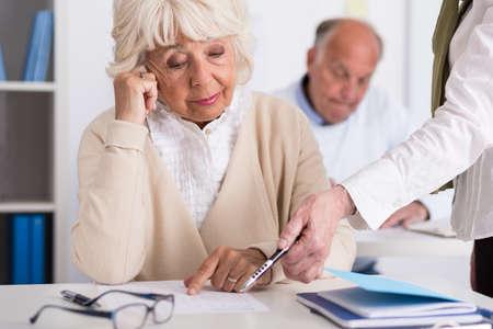 educators: Una más vieja mujer sentada en el escritorio en la escuela