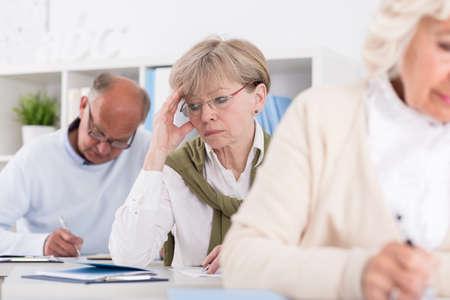 Office women: Student having headache during writing an exam