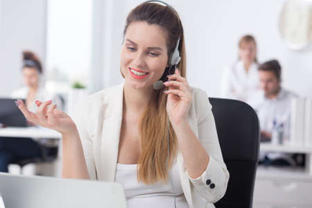 call center representative: Woman working in call center talking with customer Stock Photo
