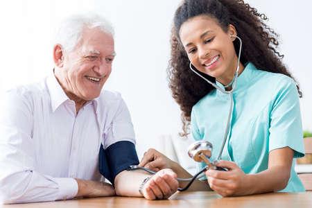 blood pressure cuff: Smiling senior man having measured blood pressure Stock Photo
