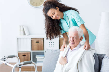 nursing assistant: Young African American doctor helping senior man
