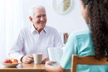 retiree: Retiree and nurse reading book at the table Stock Photo