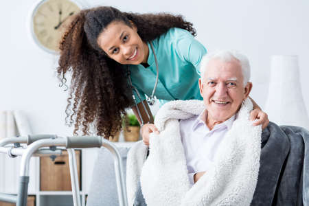 care at home: Smiling doctor caring about patient at home Stock Photo
