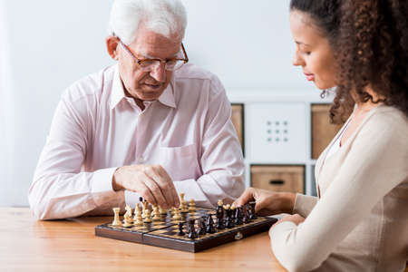 old home: Photo of retiree and caregiver playing chess