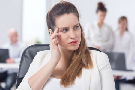woman in office: Businesswoman with migraine feeling bad at work Stock Photo