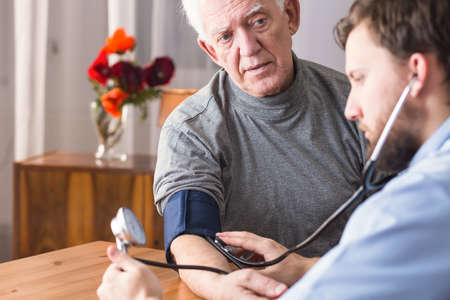 old home: Image of doctor and senior with hypertension
