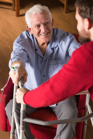 old people: Picture of son helping old disabled father Stock Photo