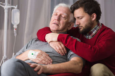 Image of last goodbye between dying father and son Stock Photo